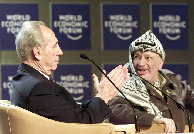 Shimon Peres, Minister of Regional Cooperation of Israel, left, applauds Palestinian leader Yasser Arafat, right, in Switzerland in 2001. (Herbert Knosowski/The Associated Press)