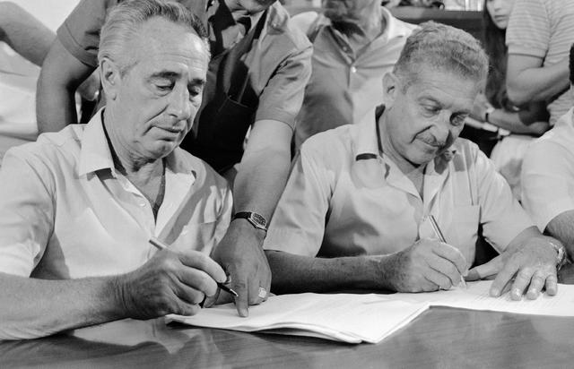 Prime Minister designate Shimon Peres and former defense minister Ezer Weizman sign an agreement between their two parties in Tel Aviv in 1984.(Anat Givon/The Associated Press)