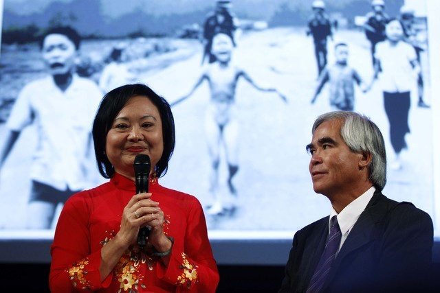 Photojournalist Nick Ut, right, and Kim Phuc attend a photography conference in 2012. Ut took the iconic 1972 Vietnam War photograph (seen in the background) of Phuc running down a road after bein ...