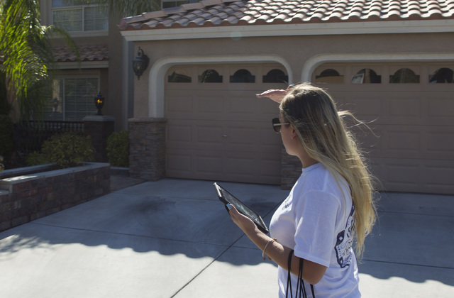 Americans for Prosperity Field Director Erinn Mahathey looks for an address on a residence as she walks door-to-door while canvassing a neighborhood for the organization in west Las Vegas on Monda ...