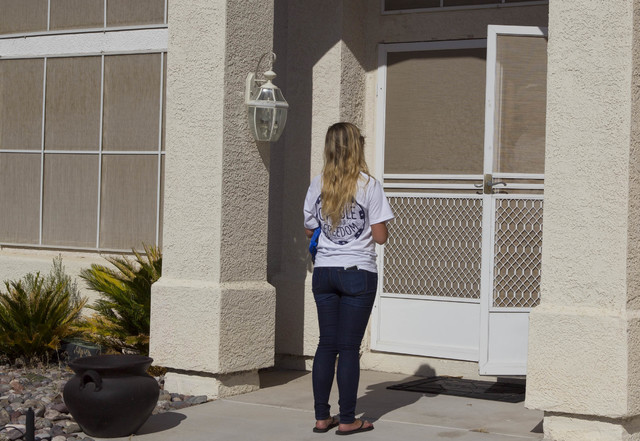 Americans for Prosperity Field Director Erinn Mahathey speaks to a person at a residence as she walked door-to-door while canvassing for the organization in west Las Vegas on Monday, Aug. 29, 2016 ...