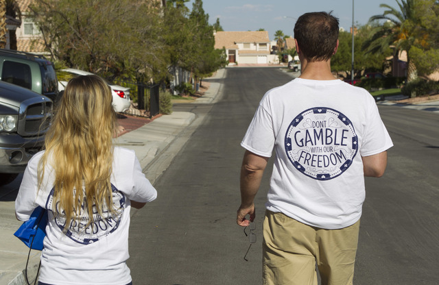 Tim Phillips, right, president of Americans for Prosperity and Field Director Erinn Mahathey walk door-to-door while canvassing a neighborhood for the organization in west Las Vegas on Monday, Aug ...