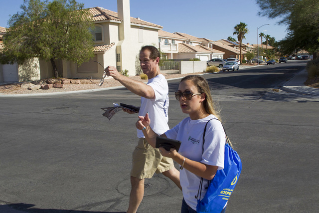 Tim Phillips, left, president of Americans for Prosperity and Field Director Erinn Mahathey walk door-to-door while canvassing a neighborhood for the organization in west Las Vegas on Monday, Aug. ...