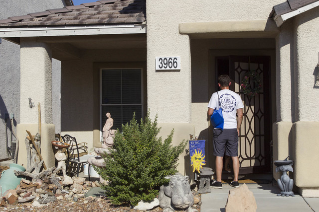 Americans for Prosperity volunteer Roger Pattison speaks to a woman while going door-to-door for the organization in a neighborhood in west Las Vegas on Monday, Aug. 29, 2016. (Richard Brian/Las V ...