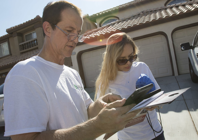 Tim Phillips, left, president of Americans for Prosperity and Field Director Erinn Mahathey check their routes on a tablet while canvassing a neighborhood for the organization in west Las Vegas on ...