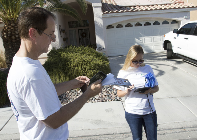 Tim Phillips, left, president of Americans for Prosperity and Field Director Erinn Mahathey update their routes on a tablet while canvassing a neighborhood for the organization in west Las Vegas o ...