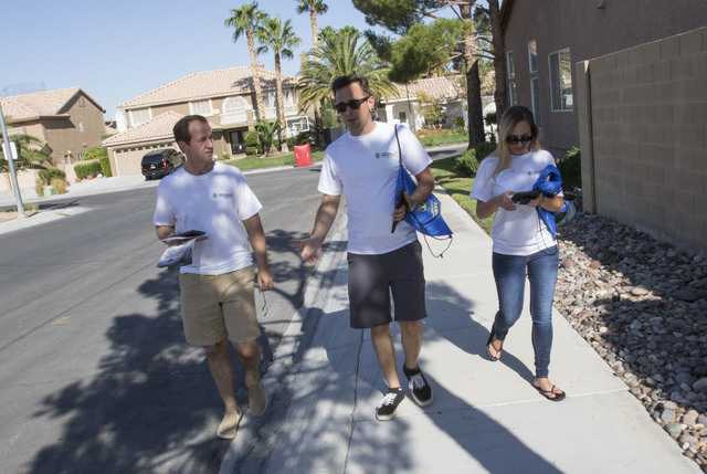 Tim Phillips, left, president of Americans for Prosperity, is joined by Field Director Erinn Mahathey, right and volunteer Roger Pattison as they canvass a neighborhood for the organization in wes ...