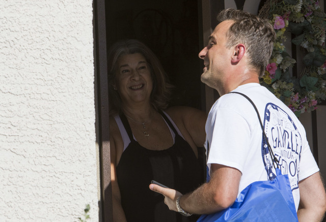 Americans for Prosperity volunteer Roger Pattison, right, speaks to a woman while going door-to-door for the organization in a neighborhood in west Las Vegas on Monday, Aug. 29, 2016. (Richard Bri ...