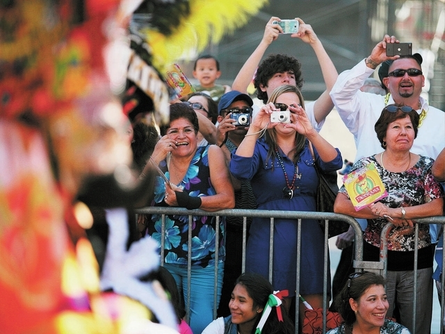 People take photographs of the Fiesta Las Vegas Latino Parade Saturday, Sept. 14, 2013, in Las Vegas. The parade, which traveled north on 4th Street downtown past the Fremont Street Experience, ki ...