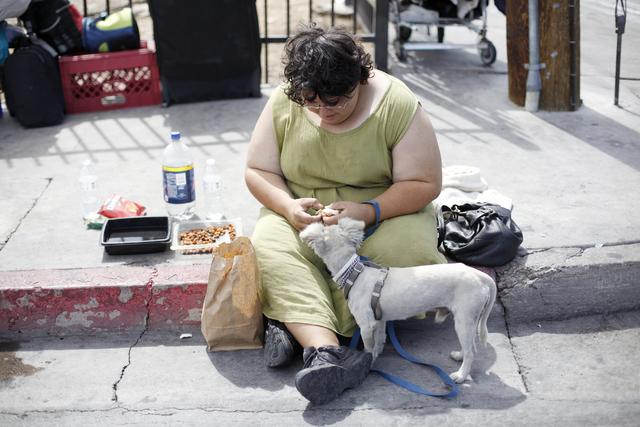 Elizabeth Smith, who is homeless, feeds her dog Bam Bam on Monday, Sept. 19, 2016, on Foremaster Lane in Las Vegas. (Rachel Aston/Las Vegas Review-Journal) Follow @rookie__rae