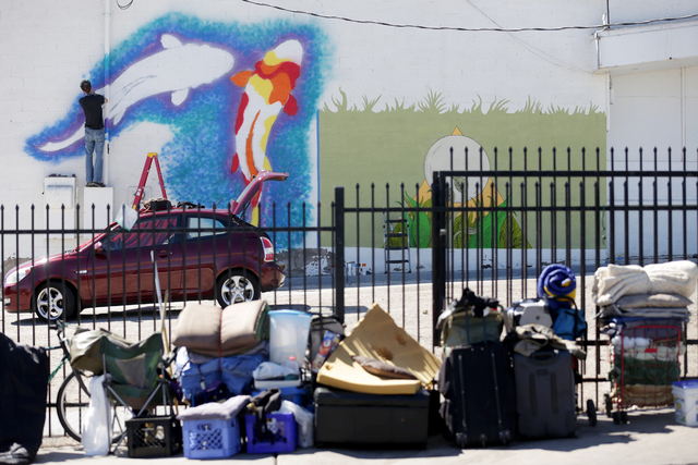 Homeless belongings are seen in the foreground as an artist paints a mural for the Life Is Beautiful Festival on a property on the corner of Foremaster Lane and Main Street on Monday, Sept. 19, 20 ...