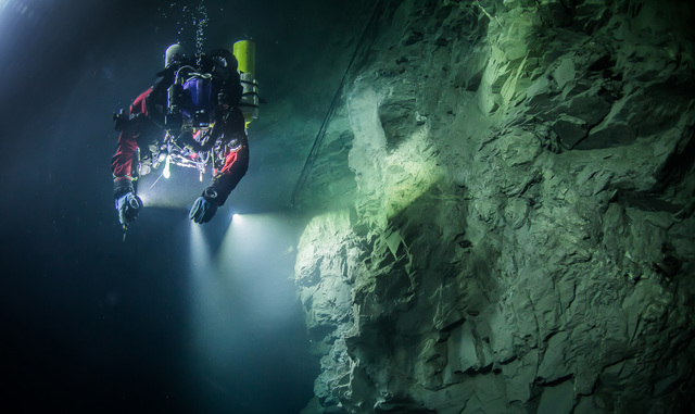 In this underwater photo taken Aug. 21, 2015, in the flooded Hranicka Abyss, Czech Republic, Polish explorer Krzysztof Starnawski is seen examining the limestone crevasse and preparing for a 2016  ...