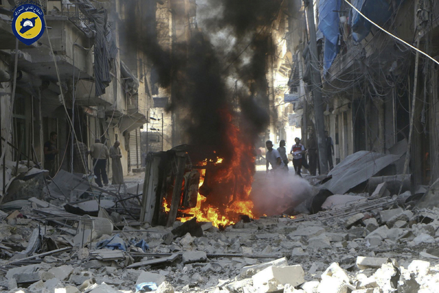 In this photo provided by the Syrian Civil Defense group known as the White Helmets, Syrians inspect damaged buildings after airstrikes by government helicopters on the rebel-held Aleppo neighborh ...