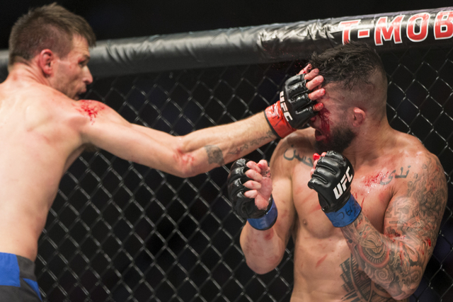 Tim Means, left, slaps Sabah Homasi in the welterweight bout during UFC 202 at T-Mobile Arena on Saturday, Aug. 20, 2016, in Las Vegas. Means won by technical knockout in the second round. (Erik V ...