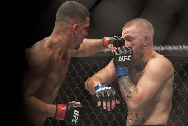 Nate Diaz, left, lands a left punch against Conor McGregor in the welterweight bout during UFC 202 at T-Mobile Arena on Saturday, Aug. 20, 2016, in Las Vegas. McGregor won by majority decision. Er ...