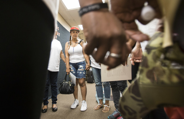 Friends and family of Roland Pleasant including his mother, Roberta Garcia, embrace hands as they gather for a prayer in honor of National Day of Remembrance at Solutions Wellness on Sunday, Sept. ...