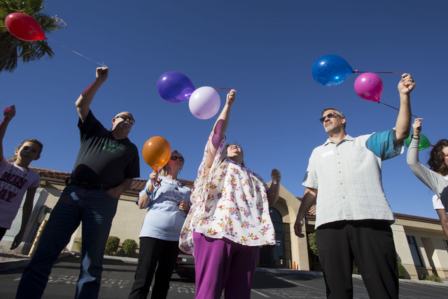 Steve Patterson, from left, Sharon Gentile, Terri Bryson, and Scott Bryson gather with others as they prepare to release balloons in honor of National Day of Remembrance at Solutions Wellness on S ...