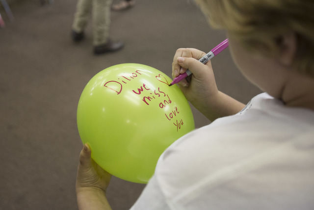 Eleven-year-old Sarah Patterson writes a message on a balloon in memory of her brother Dillon, who was murdered in 2010, before releasing it in honor of National Day of Remembrance at Solutions We ...