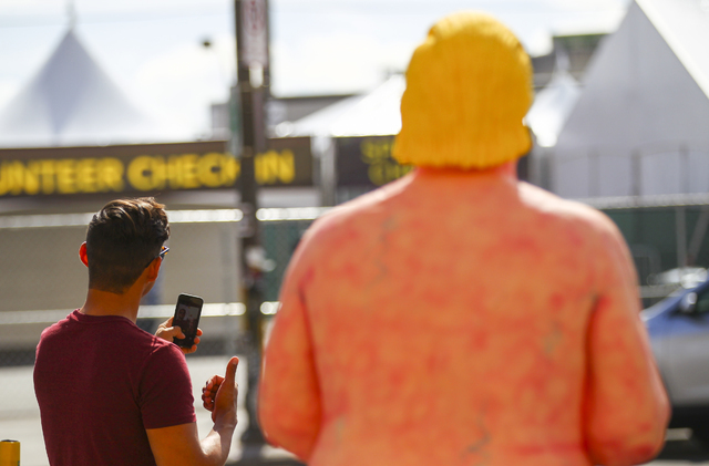 """A man takes a selfie with the art installation """"The Emperor Has No Balls,"""" depicting Republican presidential candidate Donald Trump in the nude, is shown on Sixth Street near Carson Avenue in down ..."""