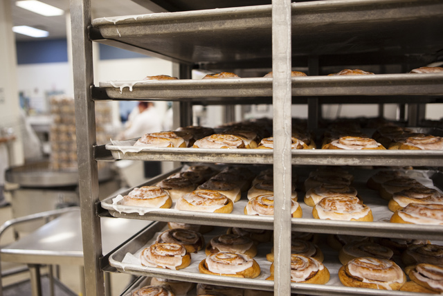 Freshly baked cinnamon rolls rest on cooling racks in the kitchen at the Clark County School District Food Service facility in Las Vegas Sept. 9. Miranda Alam/View