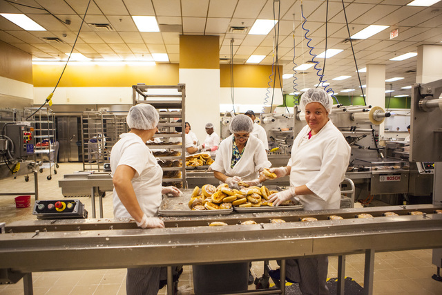 Employees at the Clark County School District Food Service facility place cinnamon rolls on a conveyer belt to be wrapped and sealed in Las Vegas Sept. 9. Miranda Alam/View Follow @miranda_alam on ...