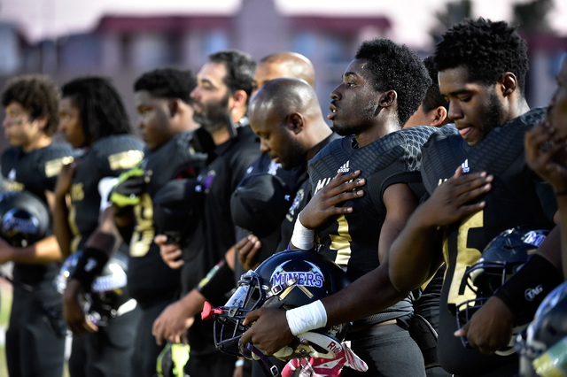 The Sunrise Mountain football team stand at attention as the American national anthem is played before a high school football game against Spring Mountain at Sunrise Mountain High School Friday, S ...