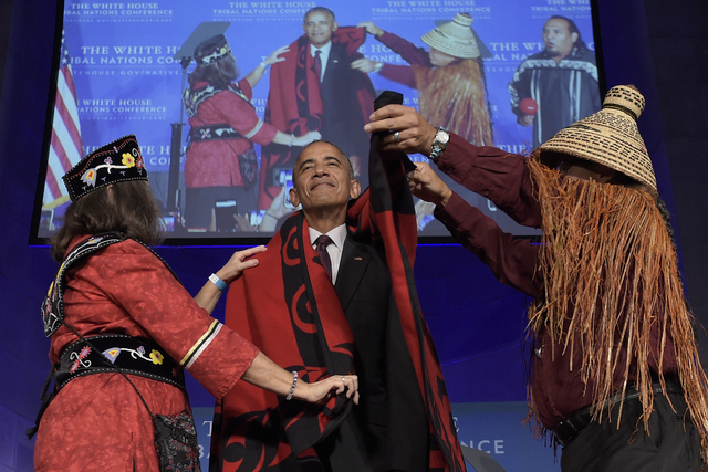 Mohegan Chief Lynn Malerba, left, and Brian Cladoosby, right, President of National Congress of American Indians, cover President Barack Obama with a blanket at the 2016 White House Tribal Nations ...
