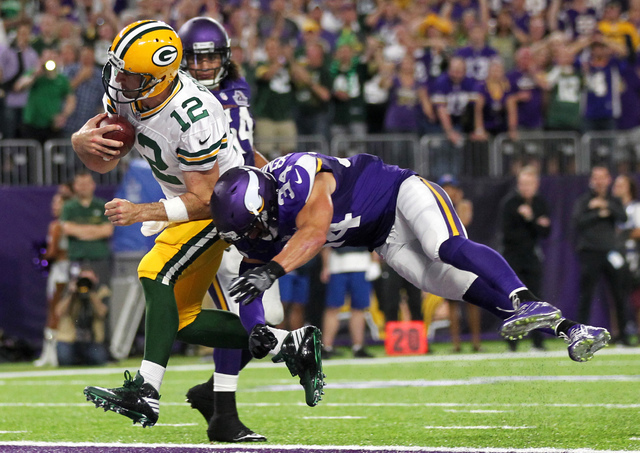 Green Bay quarterback Aaron Rodgers scores on a 10-yard touchdown run in front of Minnesota's Andrew Sendejo during the second half Sunday, Sept. 18, 2016, in Minneapolis. (Andy Clayton-King/The A ...