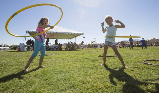 Best friends Leila Anderson, 4, left, and Sofia Sliwoski, 4, show off their hula hoop skills during the grand opening celebration of the new Paiute Park in the Mountainճ Edge community in so ...