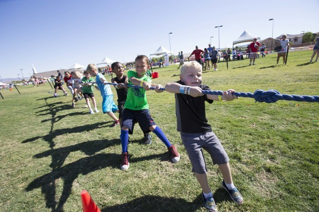 Daxton Langan, 4, leads a tug-of-war rope pull game with other youth during the grand opening celebration of the new Paiute Park in the Mountainճ Edge community in southwest Las Vegas on Sat ...