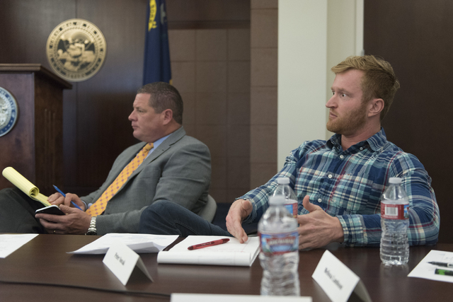 Peter Novak, CEO and chief legal officer with Cash Factory USA, right, speaks during a summit to discuss payday loans and their dangers at the Sawyer Building in Las Vegas July 8. Trent Matson, di ...