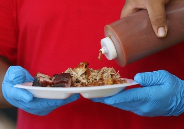 Barbecue sauce is poured over a plate of food at Rollin Smoke Barbecue at the 2015 Pigs for the Kids event at Craig Ranch Regional Park. View file photo