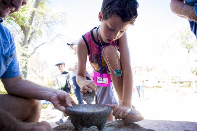 "Charlie Ferreira, 8, makes flour while saying, ""this is harder than my homework,"" during Pioneer Day at Spring Mountain Ranch State Park in Las Vegas, Sat, Sept. 17, 2016. Elizab ..."