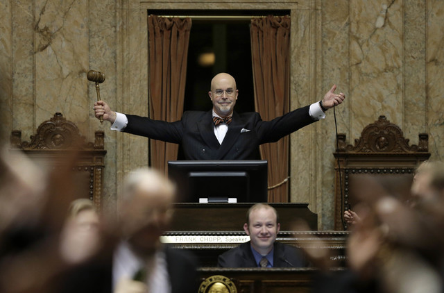 """State Rep. Jim Moeller, D-Vancouver, and Speaker Pro Tempore of the Washington House raises his gavel after declaring """"Sine Die"""" to end the regular session of the Washington Legislature, at the Ca ..."""