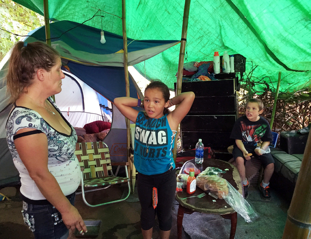 Deitra Schmer watches as her granddaughter, Andrea Brown, brushes her hair and grandson Adrian Atkinson, right, looks on in Schmer's tent in a homeless encampment in Portland, Ore., last month. (G ...