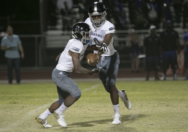 Desert Pines quarterback Randel Grimes (9) hands off the ball to Isaiah Morris during a during a varsity football game against Liberty at Liberty High School in Henderson on Thursday, Sept. 15, 20 ...