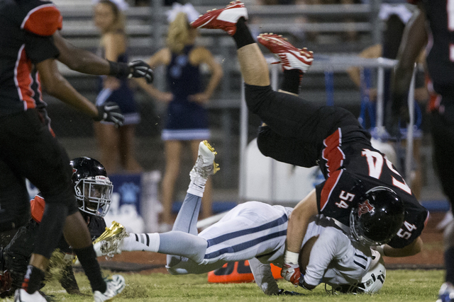 Centennial's Savon Scarver (11) is tackled by Las Vegas' Jerry Gonzales (54) in their football game at Las Vegas High School on Friday, Sept. 16, 2016, in Las Vegas. Las Vegas won 24-21. Erik Verd ...