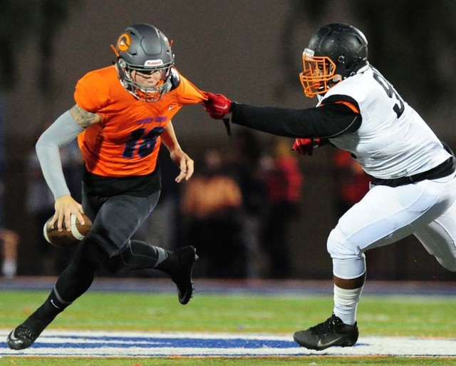 Bishop Gorman quarterback Tate Martell rushes for a first down while being chased by Cocoa, Fla.,  defensive tackle Ian Newton in the first half of their prep football game at Bishop Gorman High S ...