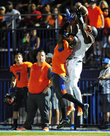 Cocoa, Fla., wide receiver Juwan Armstrong catches a first down pass while Bishop Gorman coronrback Alex Perry defends in the first half of their prep football game at Bishop Gorman High School in ...