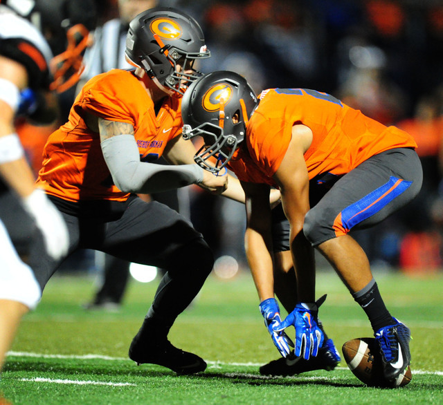 Bishop Gorman quarterback punter Tate Martell , left, and wide receiver Jimmy Telles fumble a hand-off against Cocoa, Fla.,  in the second half of their prep football game at Bishop Gorman High Sc ...