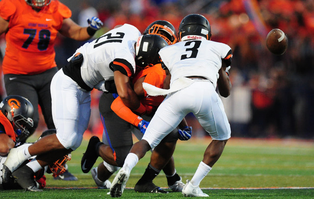 Bishop Gorman safety Austin Arnol, middle, fumbles the ball while Cocoa, Fla., cornorback Javian Hawkins (3) and linebacker Zach Beagle (21) defend in the first quarter of their prep football game ...