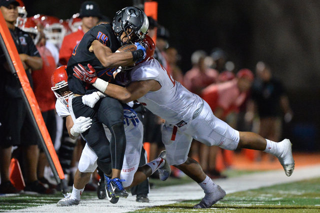 Bishop Gorman receiver Dorian Thompson-Robinson (14) is knocked out of bounds during the Bishop Gorman High School Kahuku High School game at Bishop Gorman in Summerlin on Saturday, Sept. 17, 2016 ...
