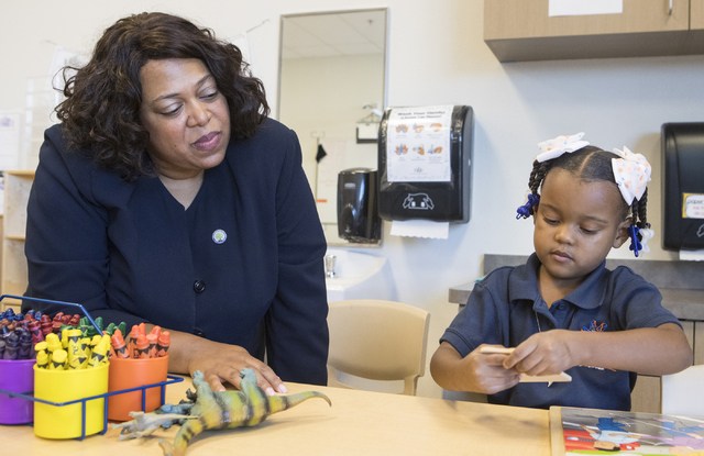 Deputy Assistant Secretary with the U.S. Department of Education Monique Chism, left, watches Mariah Wilson, 4, put a puzzle together at Mater Academy of Nevada in Las Vegas on Thursday, Sept. 15, ...