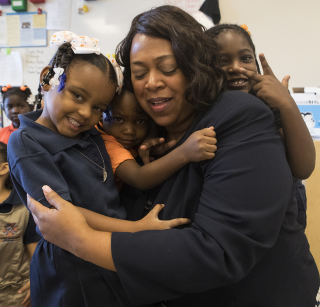 Mariah Wilson, from left, Lyris Miles, and Dylan Allison, all 4, hug Deputy Assistant Secretary with the U.S. Department of Education Monique Chism at Mater Academy of Nevada in Las Vegas on Thurs ...
