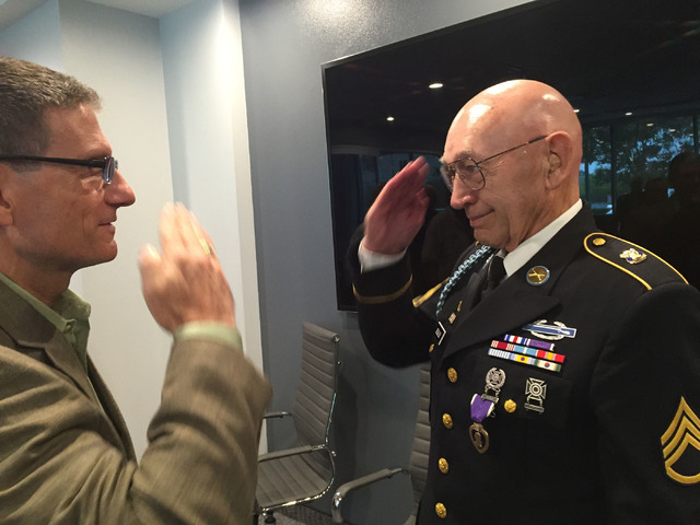 Army Korean War veteran Warren Sessler salutes Rep. Joe Heck, who is an Army Reserve brigadier general, after Heck presented him with a Purple Heart medal following a veterans meeting in Henderson ...