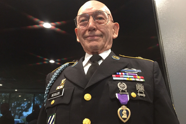Army Korean War veteran Warren Sessler stands at attention after receiving a Purple Heart medal  following a veterans meeting in Henderson Aug. 24, 2016, more than 63 years after he was wounded in ...