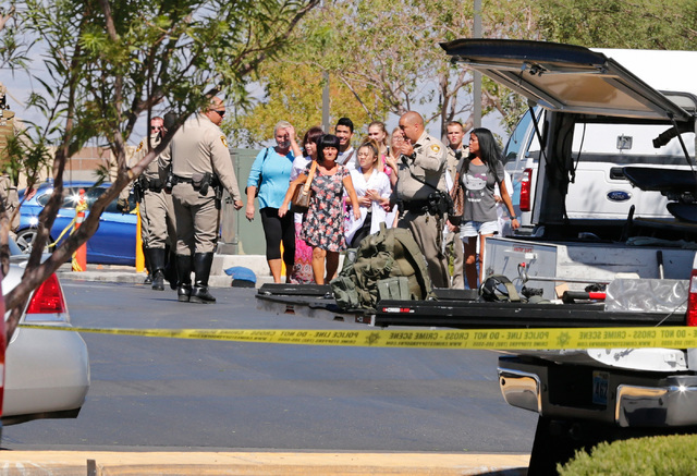 Police escorts evacuated people from a strip mall's parking lot near Rainbow Blvd. in Las Vegas, Sunday, Sept. 25, 2016, after a shooting inside a Starbucks at a southwest valley strip mall.  (Chi ...
