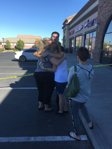 (Rachel Hershkovitz/Las Vegas Review-Journal) Will Wright, 19, hugs his mother and sister after being released by police. Wright was working the cash register in the Starbucks when the shooting began.