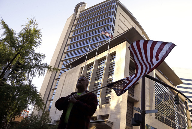 A protester, who would only identify himself as Robert, flies an upside down American flag outside the federal courthouse in Portland, Ore., Tuesday, Sept. 13, 2016. (Don Ryan/The Associated Press)