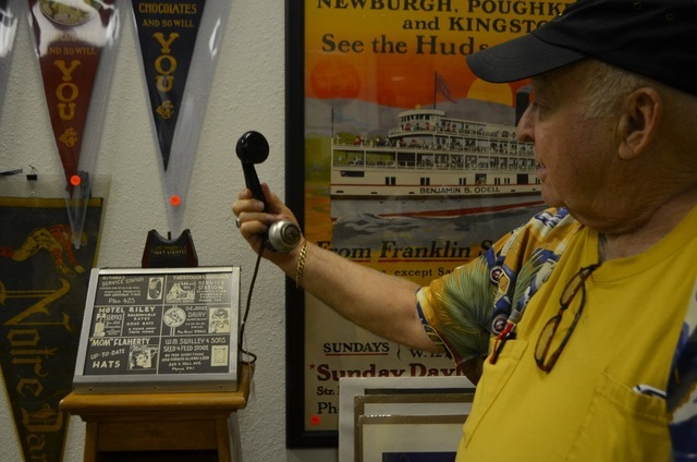 Peter Sidlow demonstrates a cigarette lighter telephone, among antiques he stocks at Peter J. Sidlow — Advertising Antiques in the back room of The Ribbon Store, 572 S. Decatur Blvd, on Aug. 25. ...